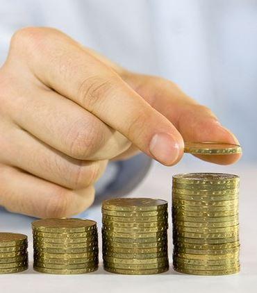 mão segurando moedas empilhadas