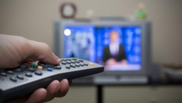 mão segurando controle remoto e propaganda eleitoral passando na televisão