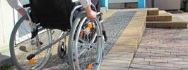Pessoa em cadeira de rodas subindo rampa