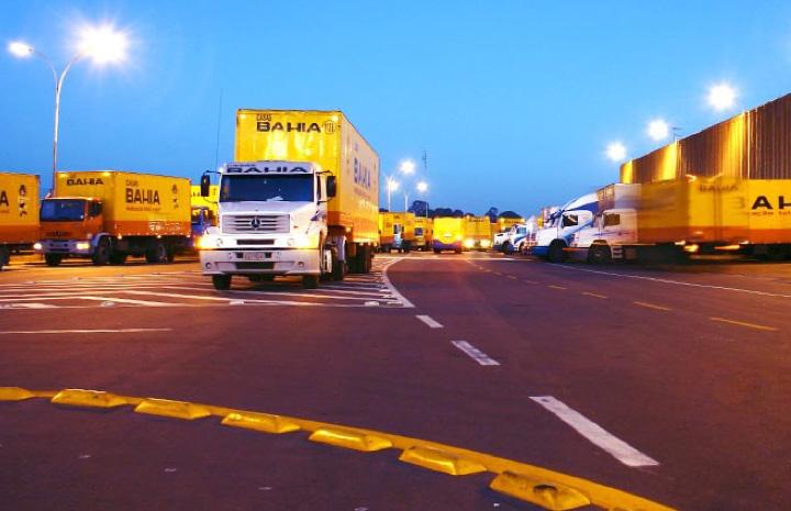 Foto do Centro de Distribuição da Casas Bahia com diversos caminhões no pátio.