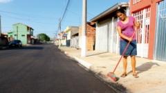 A dona de casa Luzia Vieira Machado varre a frente da sua casa após a colocação do pavimento novo, ela diz que agora parece que a rua está até mais larga e a casa fica mais bonita