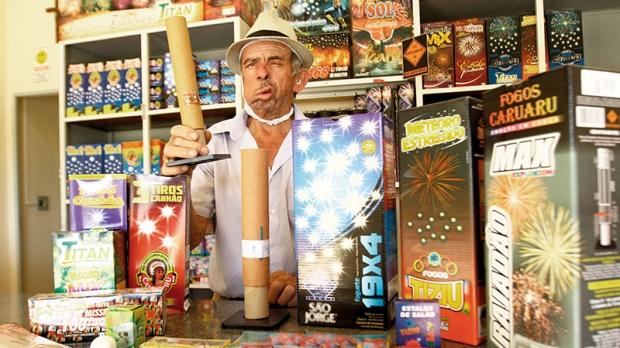 José dos Santos Carriel, dono do único comércio do ramo legalizado na cidade, mostra modelos de fogos que comercializa