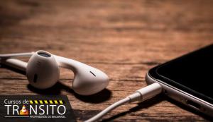 Posso dirigir usando celular com fones de ouvido?