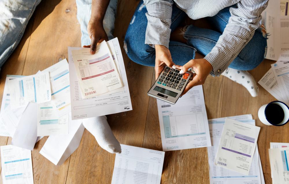 Casal segurando calculadora contas e boletos