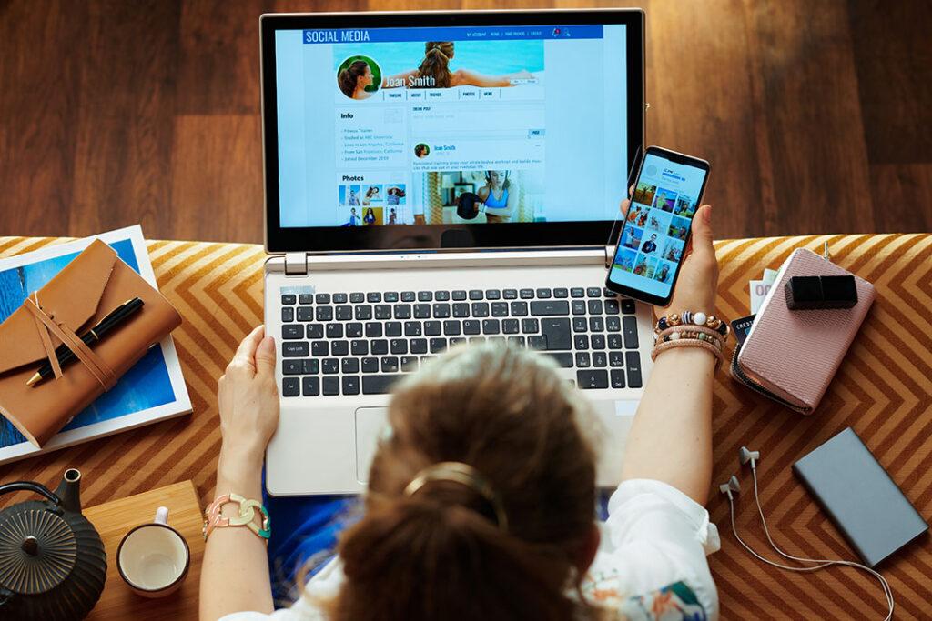 mulher olhando a tema do notebook e do celular ao mesmo tempo