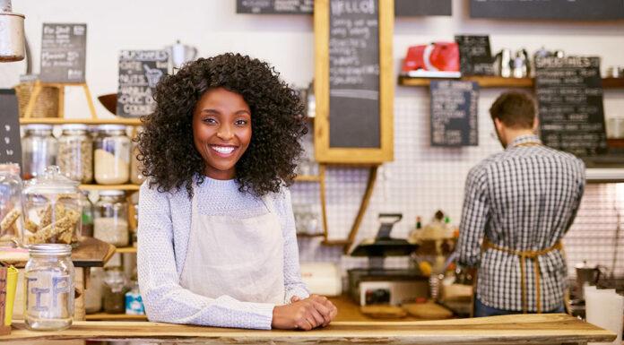 mulher sorrindo em frente ao balcão de uma loja