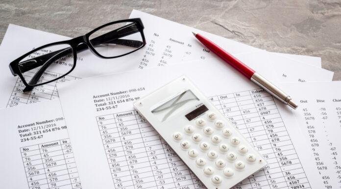 balanços bancários, um óculos, uma caneta e uma calculadora em cima de uma mesa