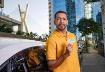 homem de camiseta amarela em frente a veículo e segurando o cartão da conta pagbank