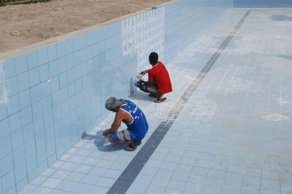 Foto de homens aplicando rejunte para piscina