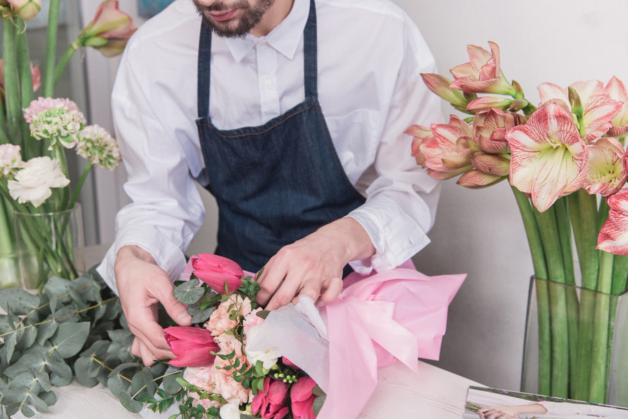 Small business male florist in flower shop making decorations and arrangements