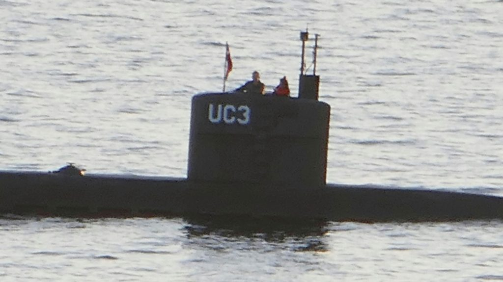 "Allegedly Swedish journalist Kim Wall stands next to a man in the tower of the private submarine ""UC3 Nautilus"" on August 10, 2017 in Copenhagen Harbor. Danish police said Sunday they searched a huge DIY submarine that sank last week in the hunt for the missing journalist who had been aboard before it sank, but no body was found. - / AFP PHOTO / Peter THOMPSON"