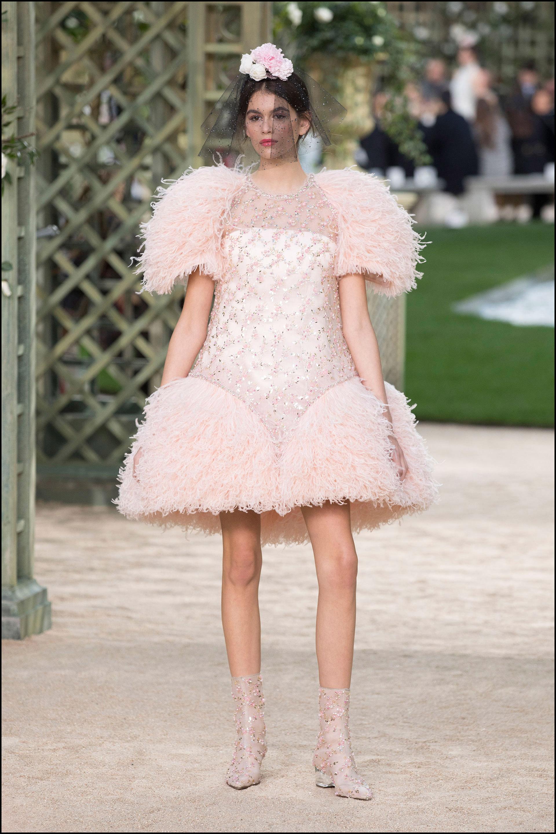Kaia Gerber con un diseño corto bordado con plumas, botas, y flores en el pelo.
