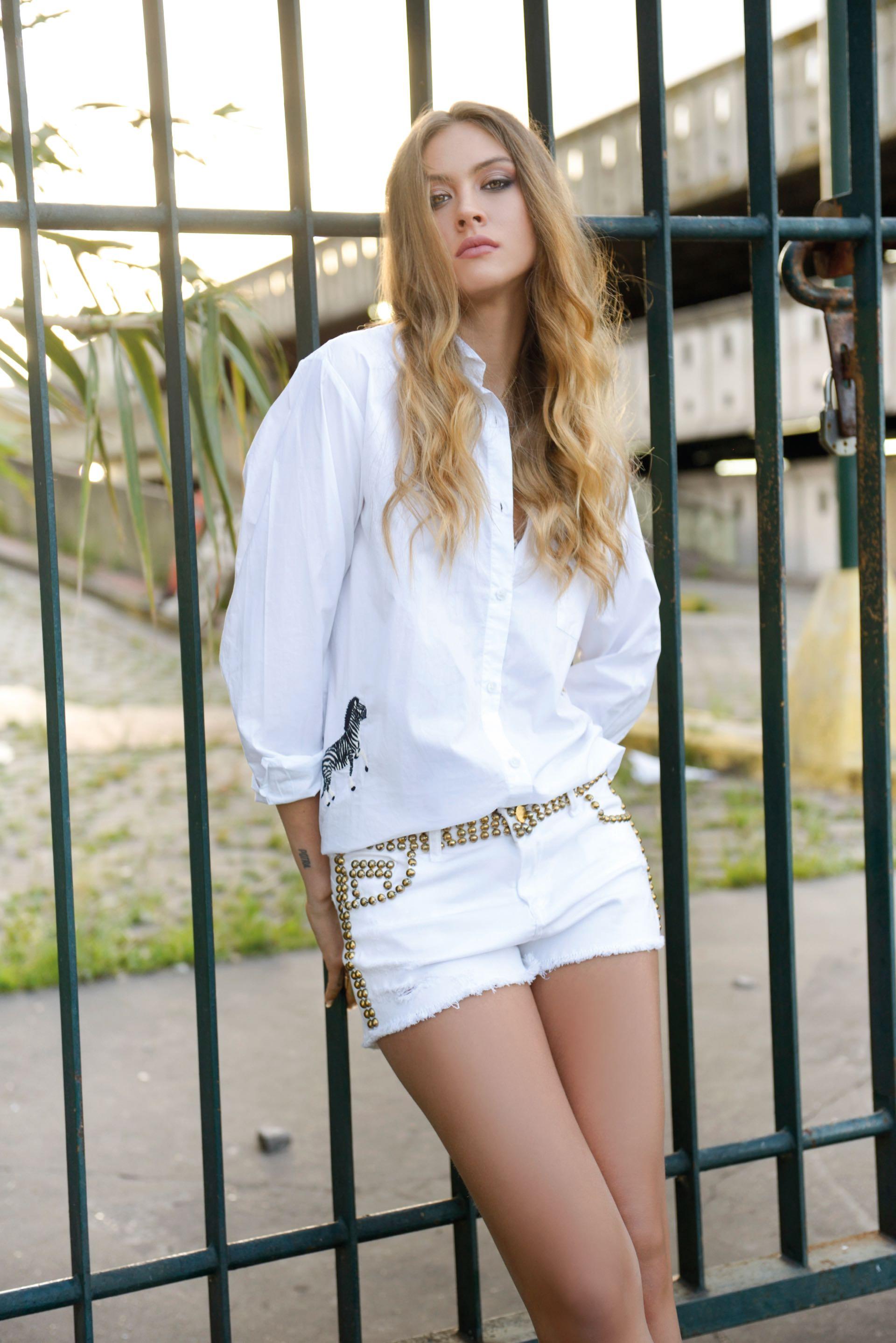 Camisa oversize con apliques bordados (Kosiuko) y short de jean blanco con tachas (Ginebra). (Foto Conejo Collins/ Para Ti)
