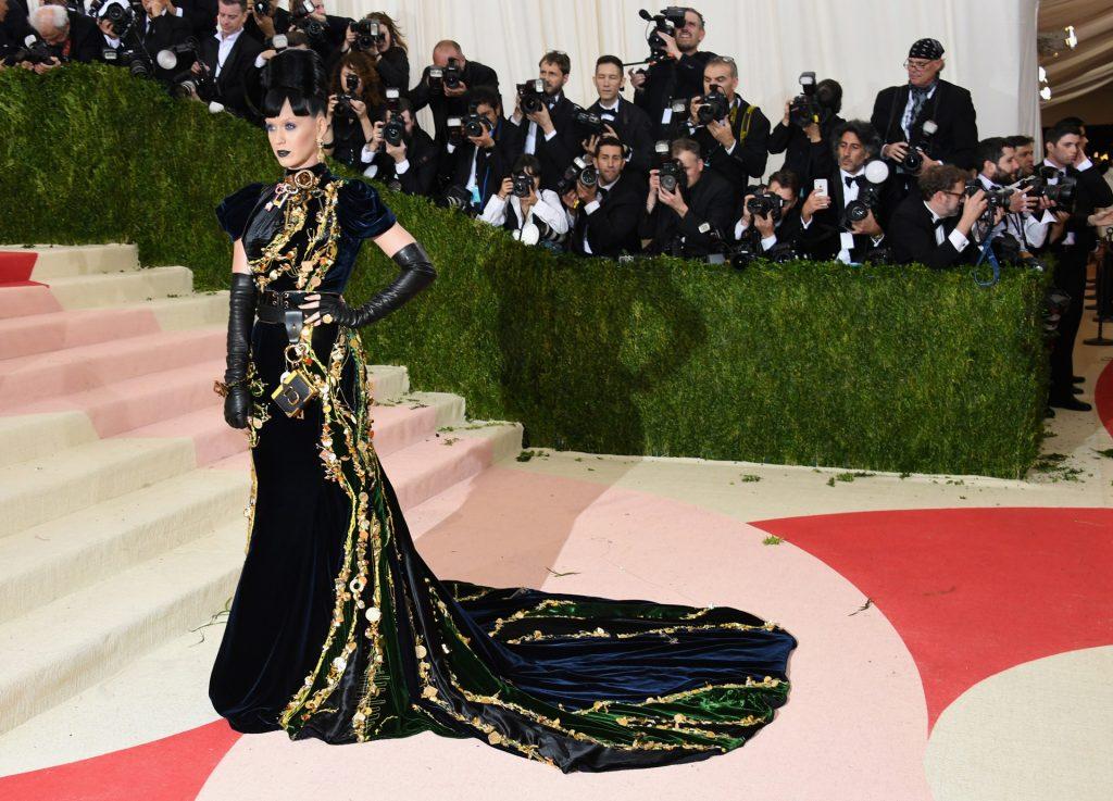 """Katy Perry siguió al pie de la letra la temática del 2016 """"La Moda en la Era de la Tecnología"""", con un peinado imponente y labios negros desfiló con un modelo negro cubierto de aplicaciones doradas metálicas, incluyendo un manojo de llaves, y un Tamagotchi (Getty)"""