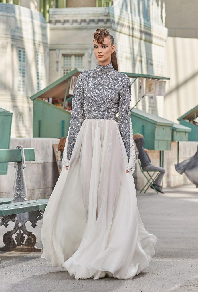 Un escote drapeado y bordado en encaje y papel de seda plateado cae en un vestido fluido. (Chanel)