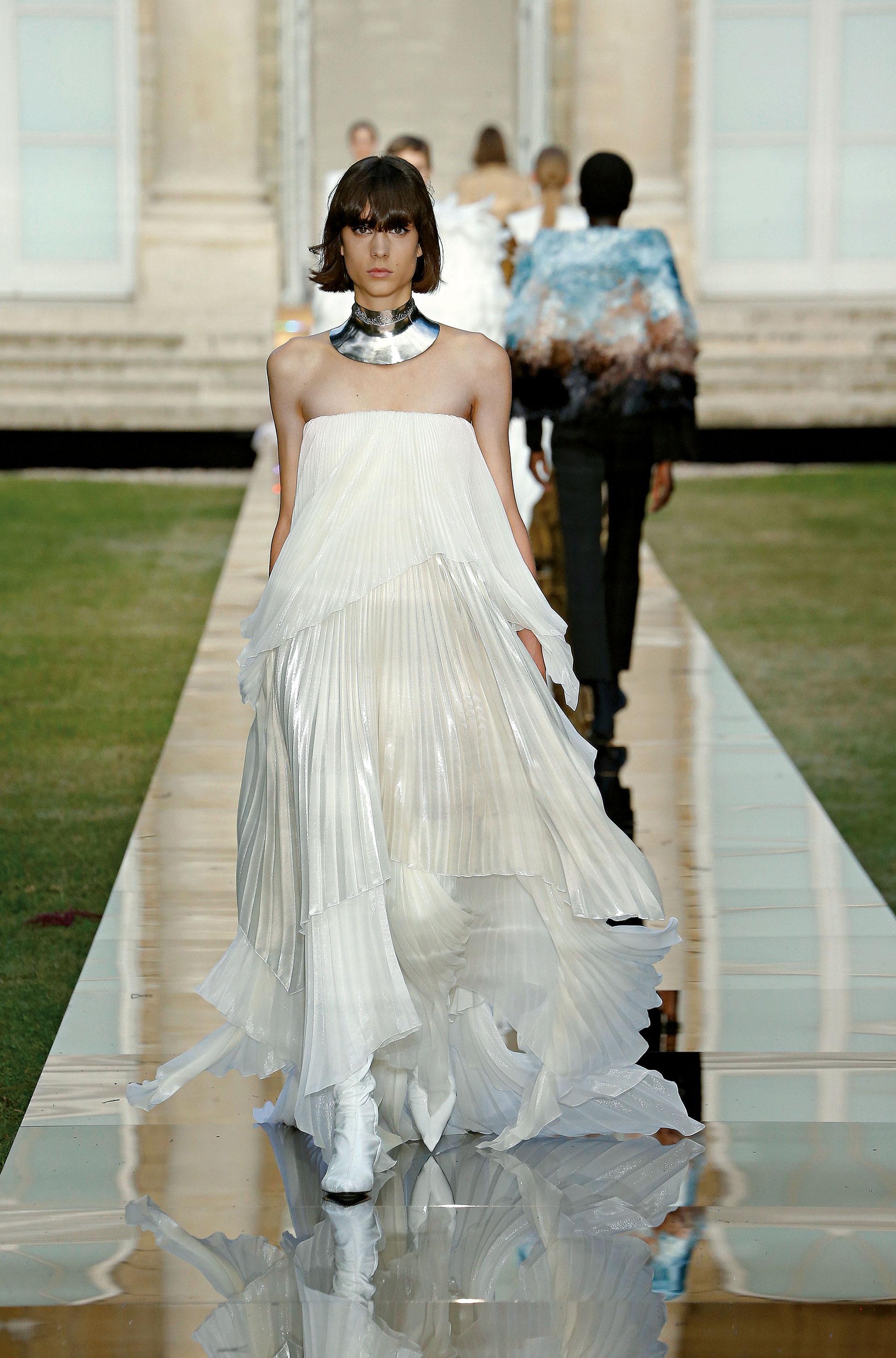 GIVENCHY. Clare Waight Keller rindió homenaje a Hubert de Givenchy con una selección de vestidos inspirados en los modelos clásicos de la firma. (Izq.) La modelo Beatriz Ronda lució un vestido strapless con capas plisadas de corte irregular.