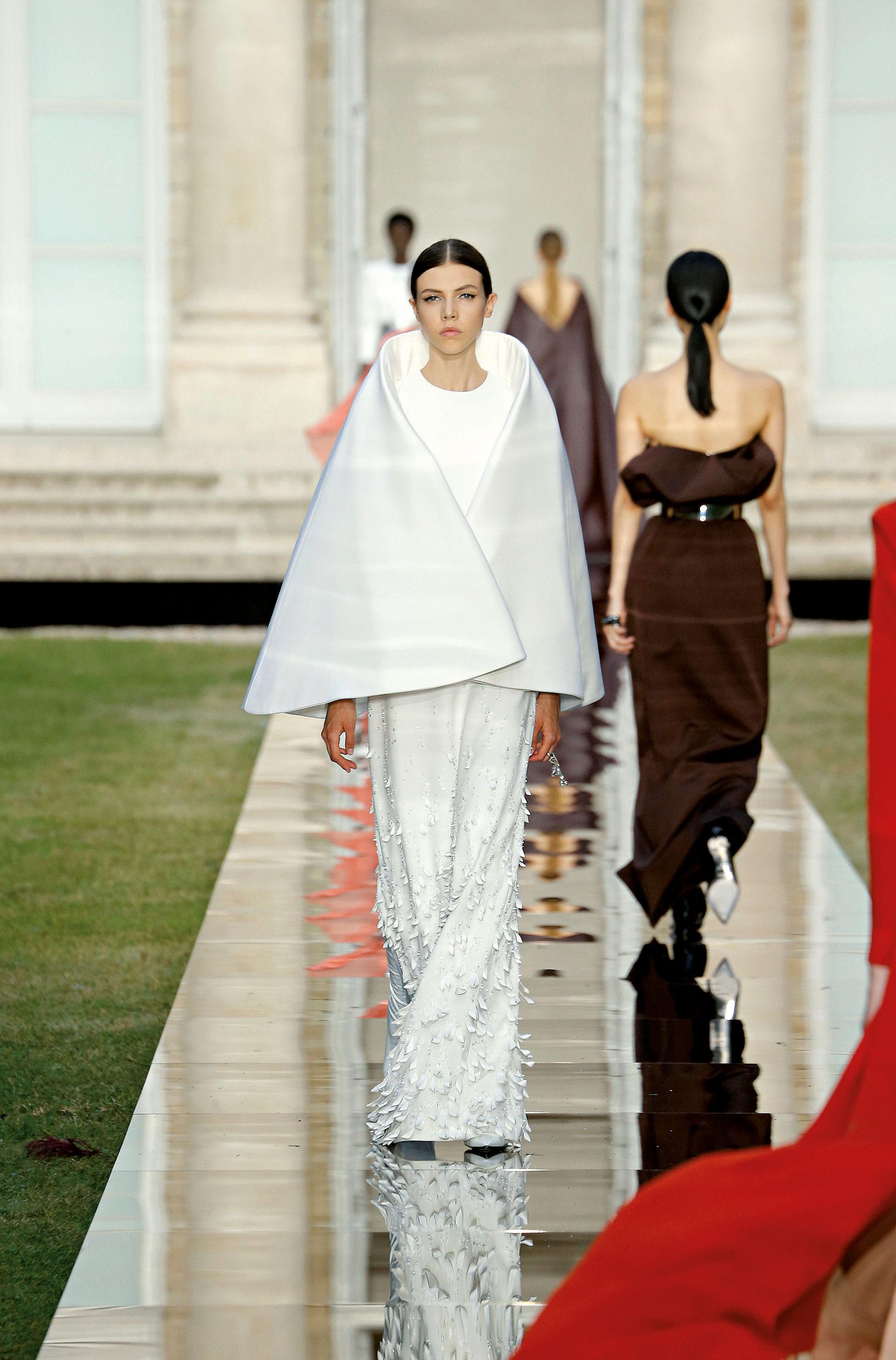Léa Julian, por su parte, paseó por la pasarela una capa de escote futurista sobre un vestido al cuerpo, de cuello redondo y falda tubo con lazos y piedras aplicados.