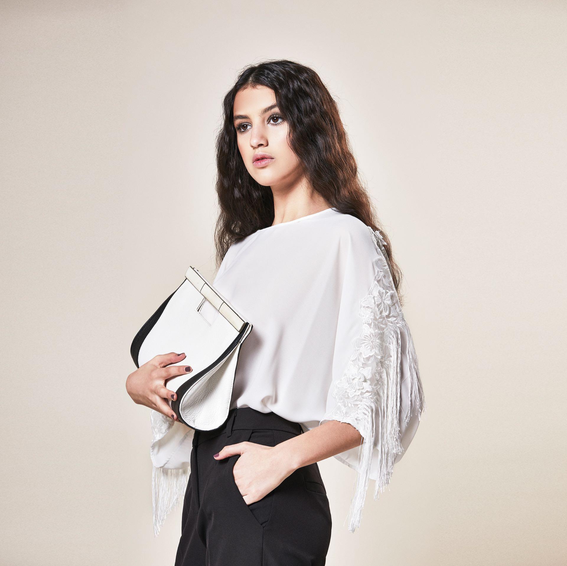 Blusa de gasa con encaje y flecos ($ 6.000, Rafael Garófalo), pantalón sastre ($ 2.400, Ossira) y clutch de cuero y nácar (Casta by Analía).