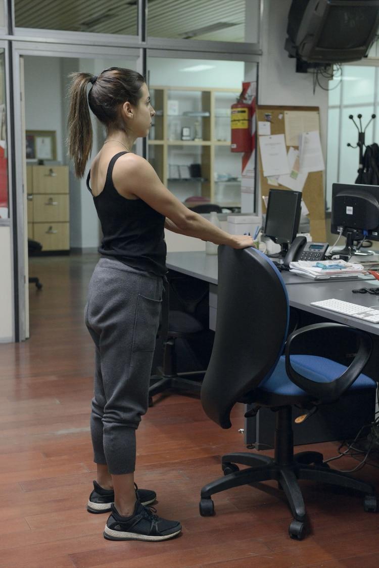 Estiramiento de la espalda. 1. De pie, apoyá las manos sobre el respaldo de la silla