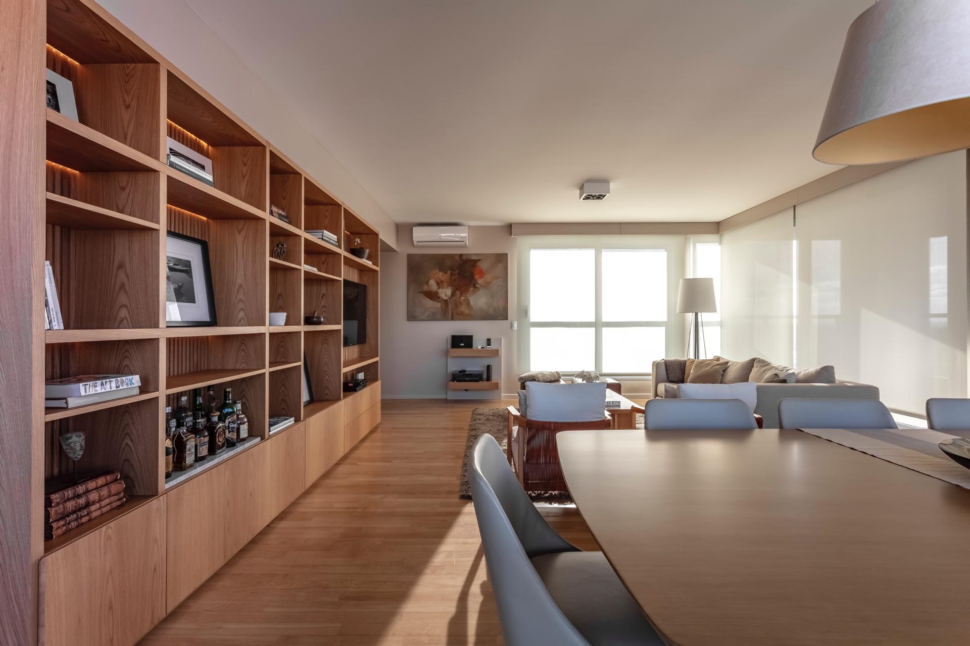 Living y comedor comparten un mismo y gran ambiente, y por ende una misma estética. El gran mueble de roble que es biblioteca y bar a la vez, los une.