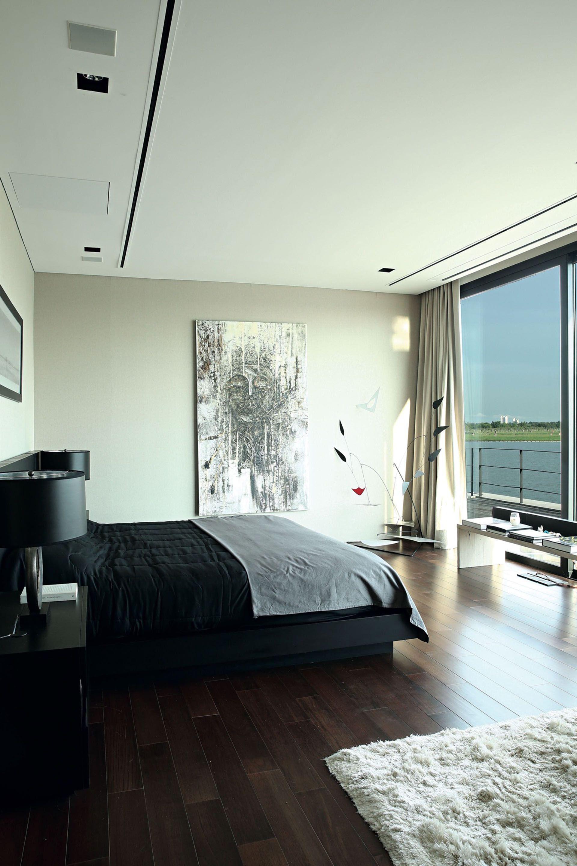 Una paleta muy estricta (gris + blanco + negro) viste el moderno cuarto principal. El ventanal que mira a la laguna es protagonista.