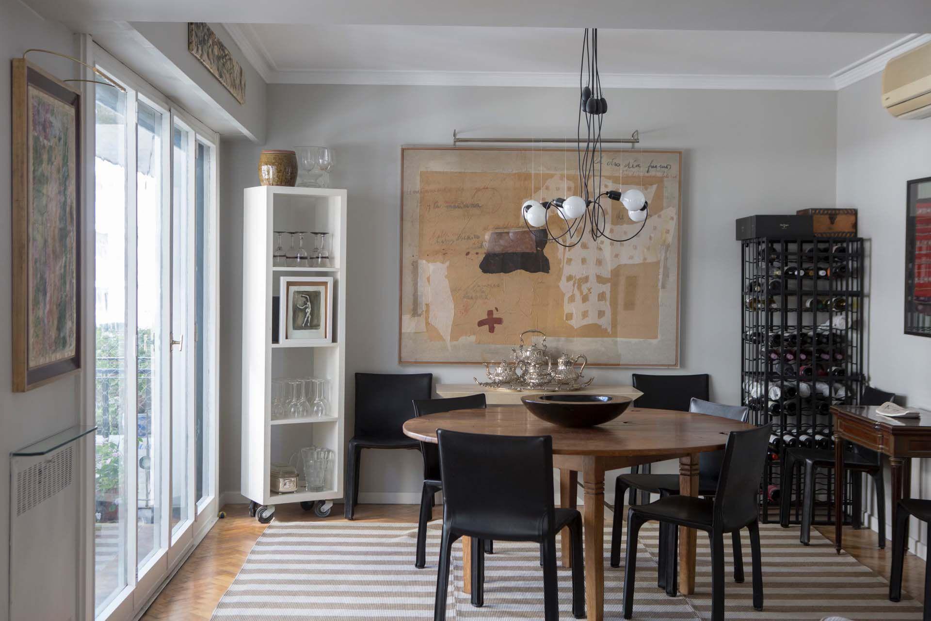 El eclecticismo del cliente se refleja también en el comedor, donde conviven sillas de diseño moderno, con una mesa rústica, arte informalista y platería europea.