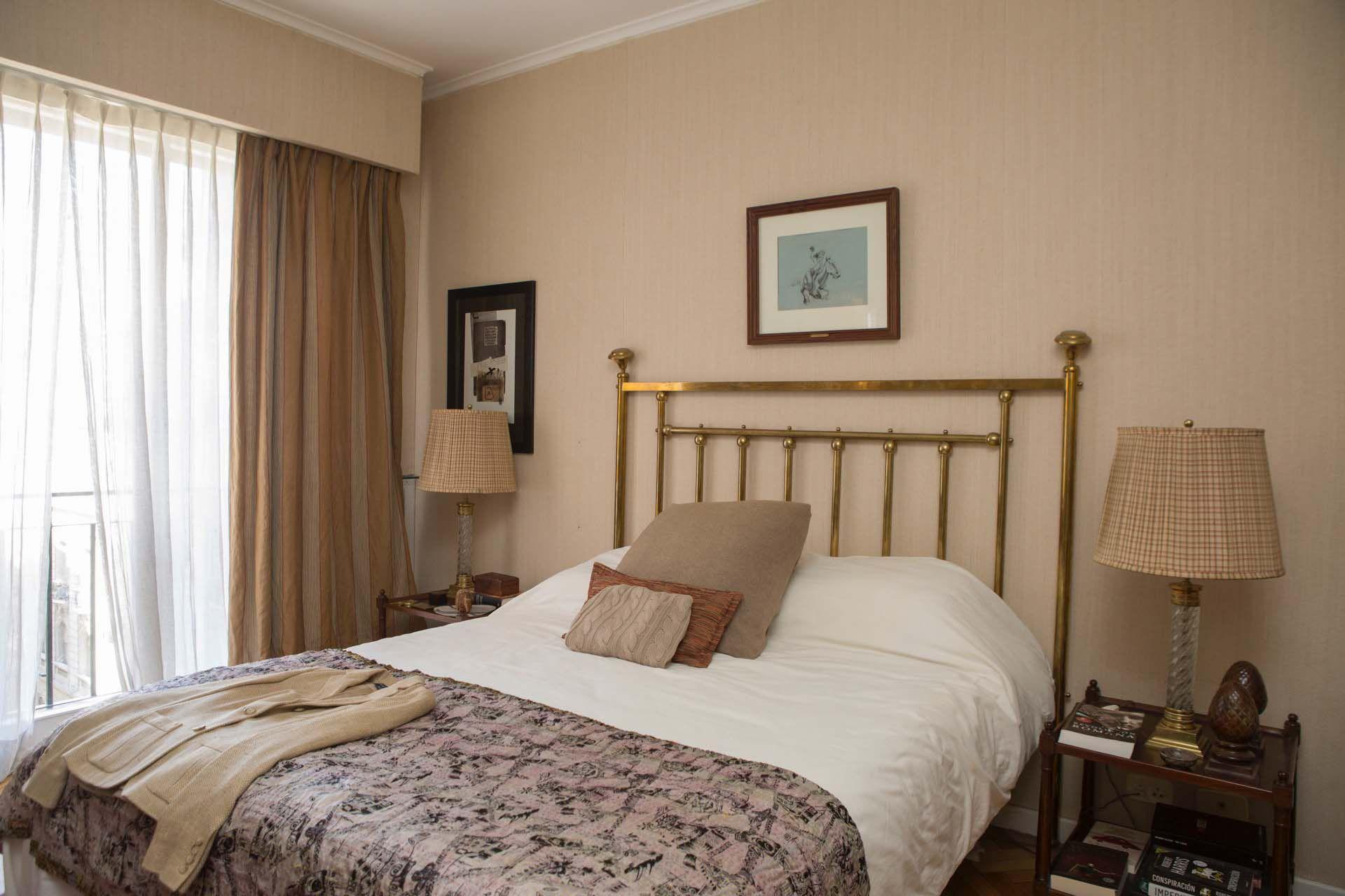 De corte más clásico, el dormitorio principal prefire la elegancia del bronce y la madera de caoba.