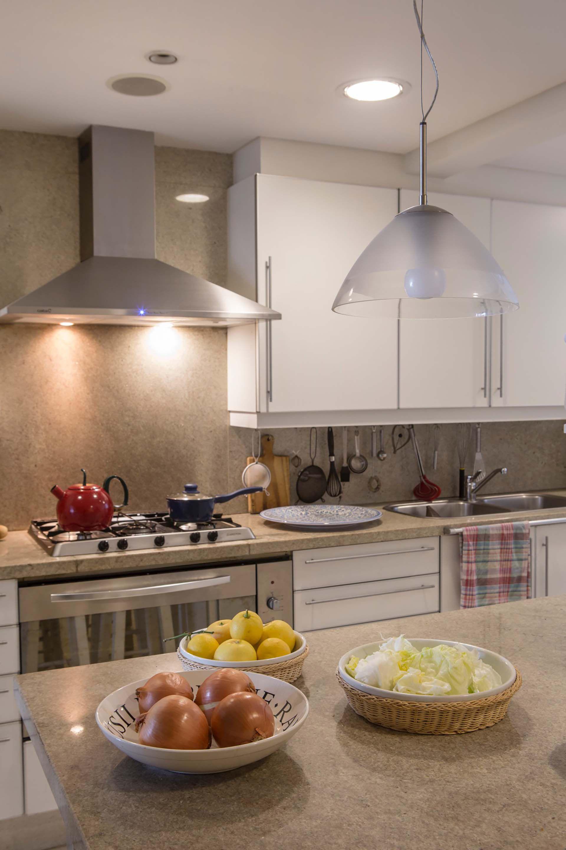 Muebles laqueados en blanco y grandes placas de granito sin pulir para la moderna cocina.