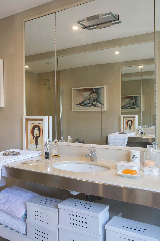 El arte también se cuela en el baño y se replica en el gran espejo pegado a filo que cubre la pared. Unas cajas decorativas permiten mantener todo en orden.