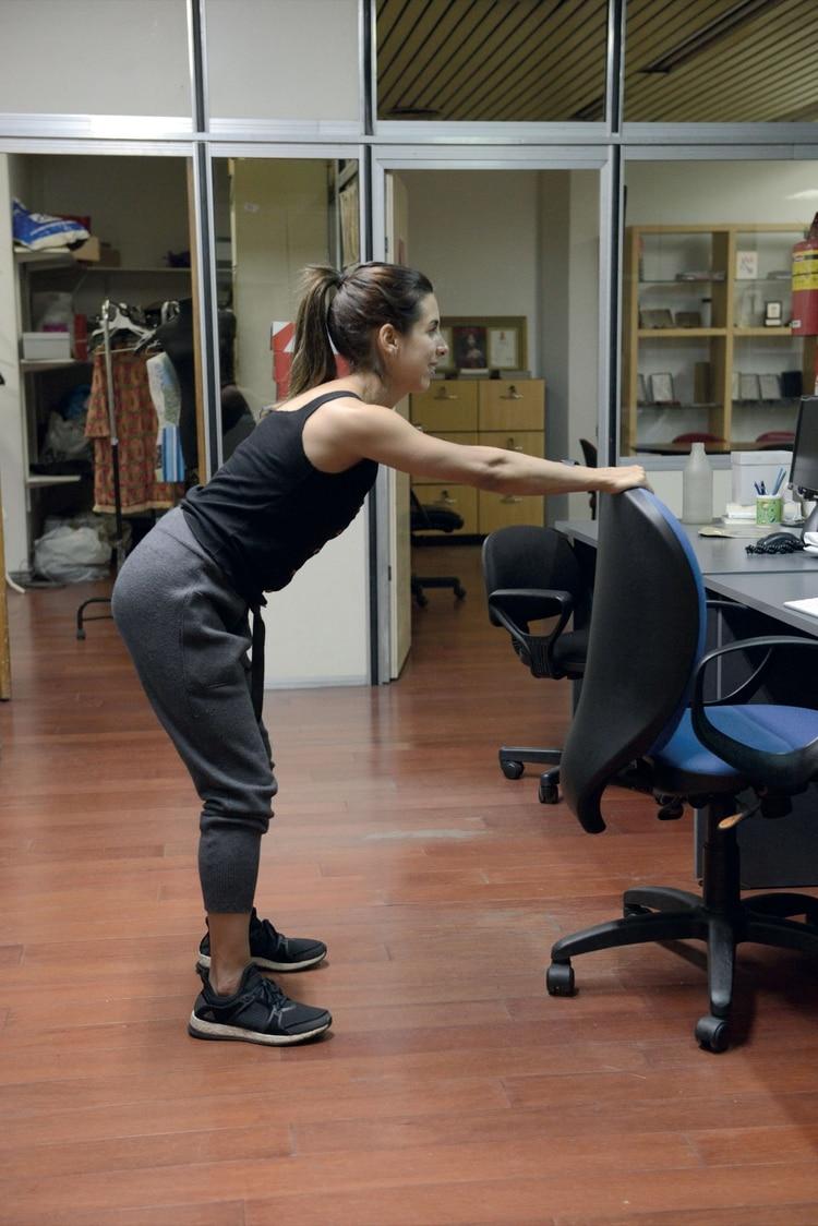 2. Separá las piernas a la altura de las caderas, flexioná las rodillas e incliná el tronco hacia adelante hasta que quede paralelo al piso.