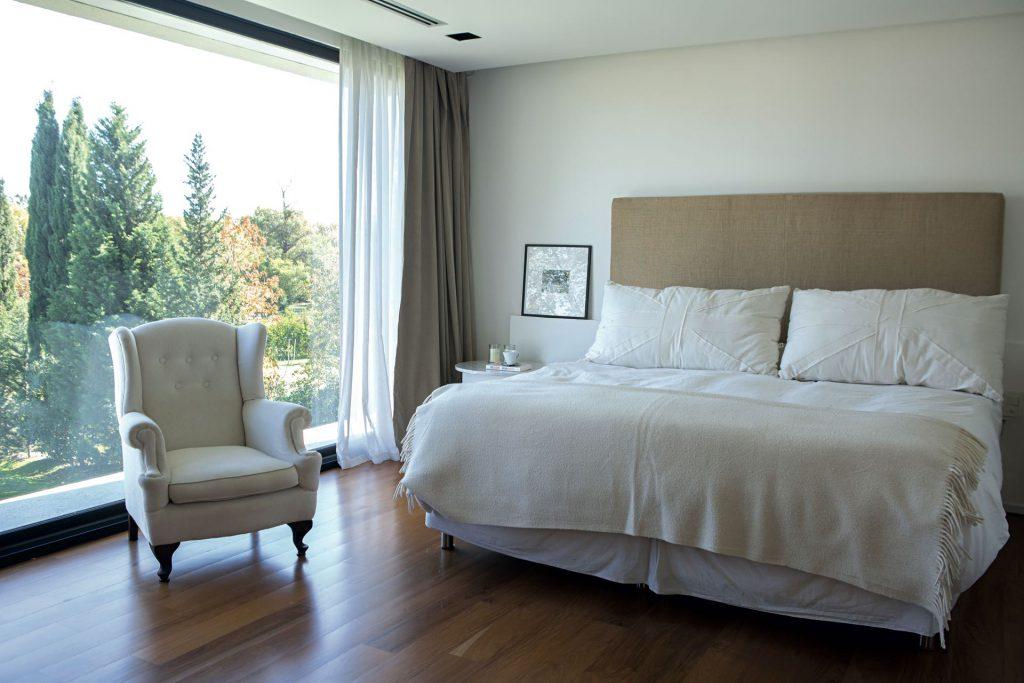 La suite tiene pisos de madera lustrados, cama con respaldo alto tapizado y mantas y almohadones blancos