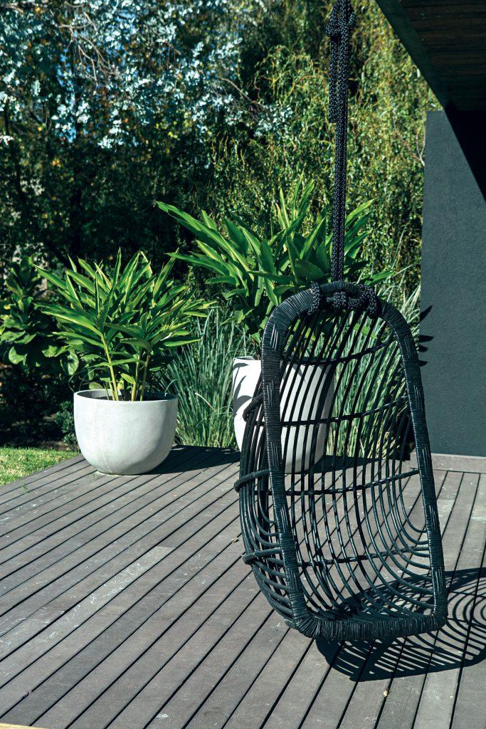 En un rincón del quincho, un sillón hamaca negro de mimbre (Design Lovers).