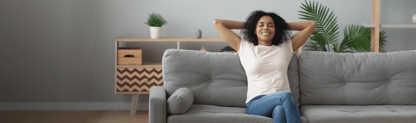 Mulher descansando em um sofá limpo e confortável na sala de casa.