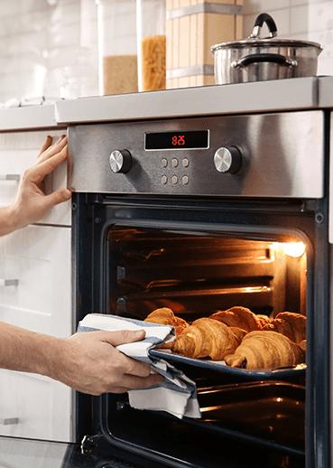 Pessoa tirando pães do forno