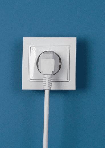 Cabo de força ligado a tomada em uma parede azul.