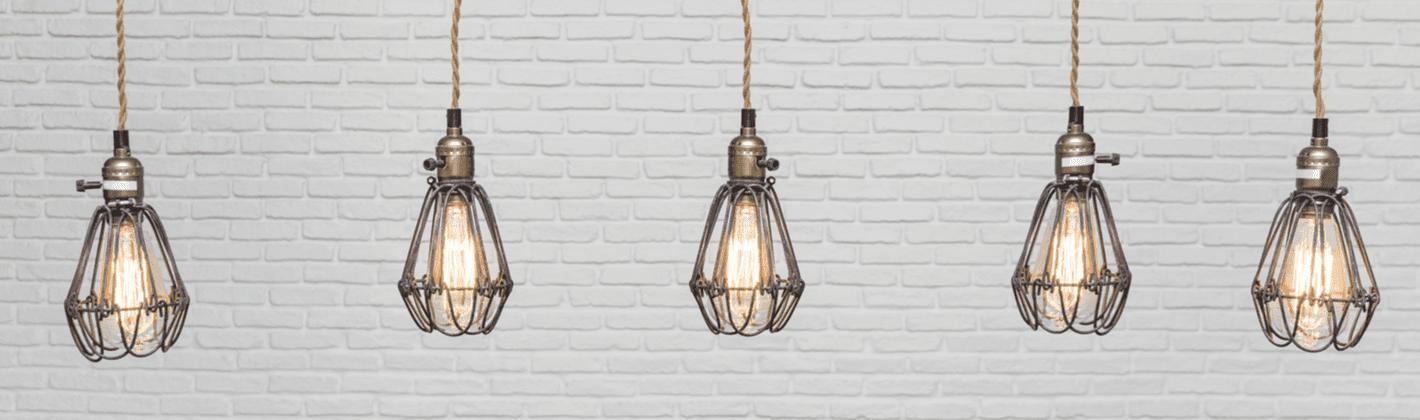 Várias luminárias suspensas com lâmpadas de filamento acesas.