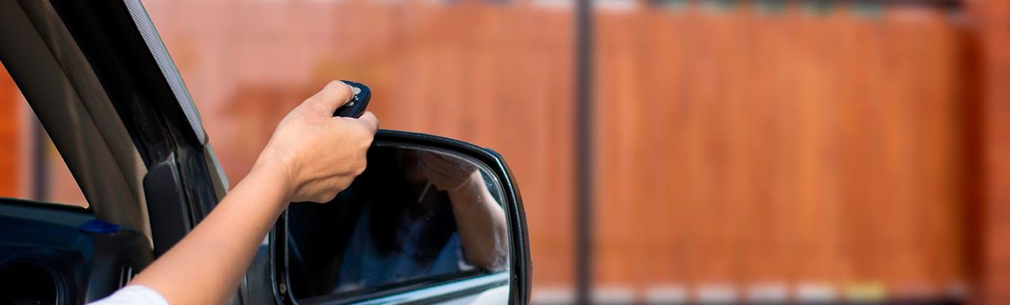 Pessoa usando um controle remoto para abrir automaticamente o portão sem sair do veículo