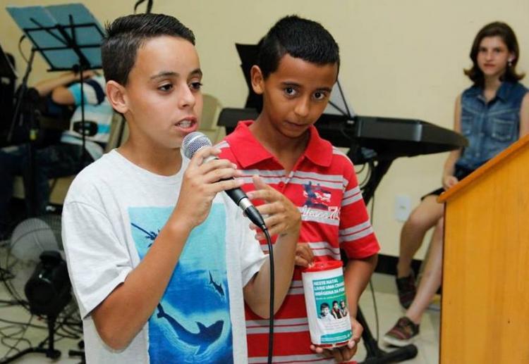 Repetindo a ação dos magos, crianças abrem seus cofres e ofertam presentes aos indígenas