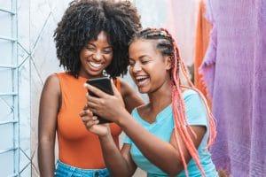 Imagem de duas mulheres sorrindo olhando algo engraçado no celular de uma delas