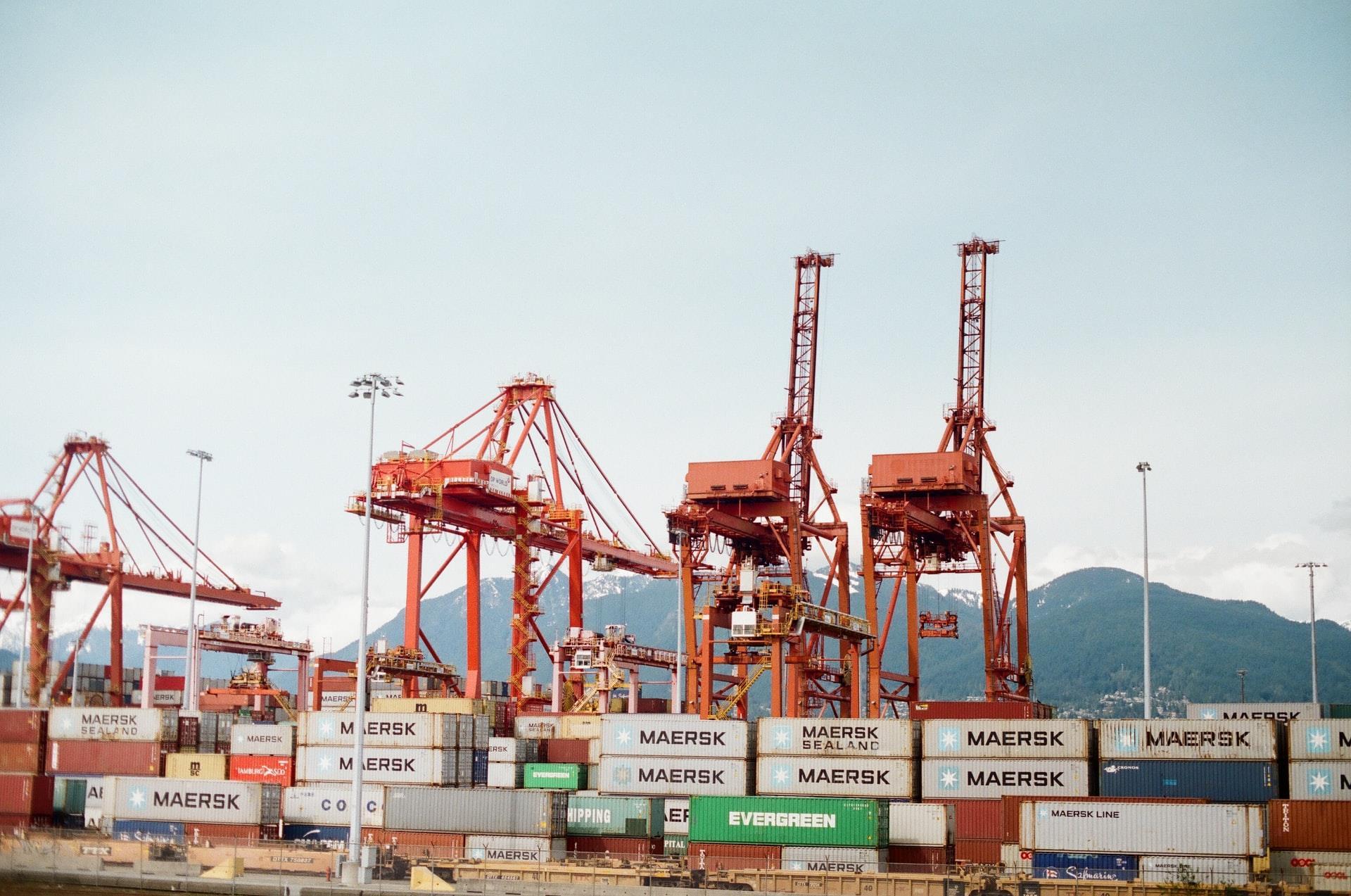 A imagem mostra um navio sendo carregado com containers em um porto.