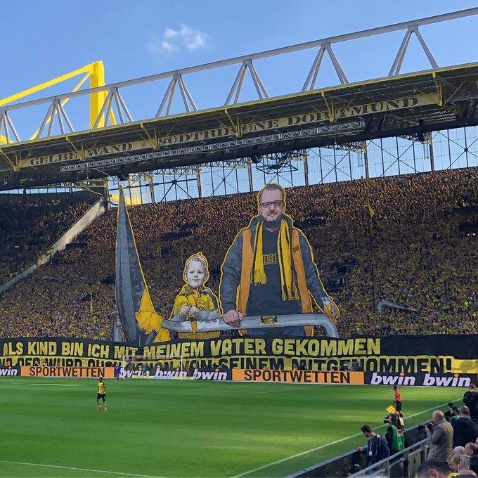 """Mosaico da torcida do Dortmund no jogo contra o Wolfsburg, em março de 2019. """"Quando criança meu pai me levou aos jogos, assim como seu pai fez com ele"""", diz o mosaico, que ilustra a tradição de uma das torcidas mais apaixonadas do mundo."""