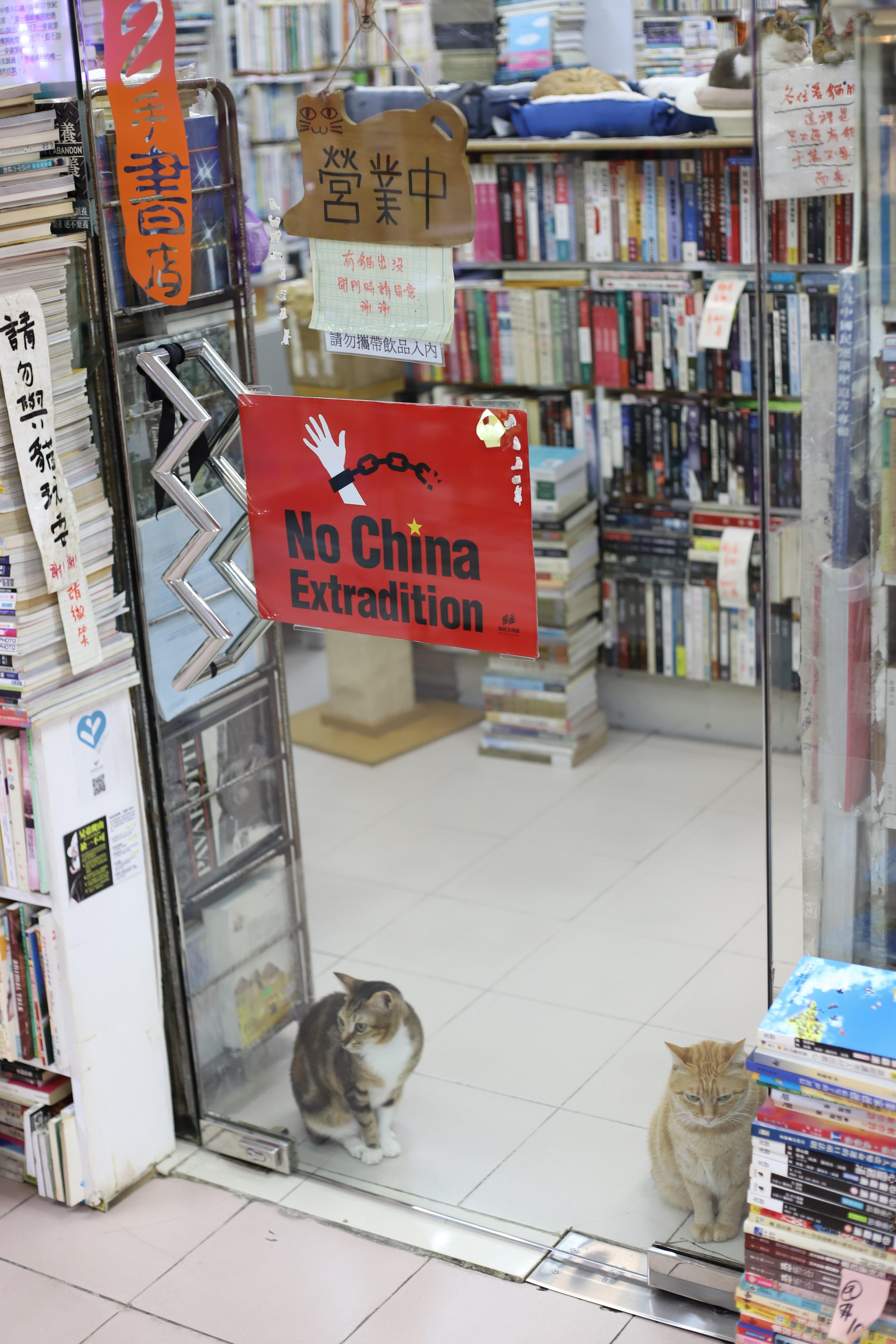 """Imagem de uma porta na qual está colado um adesivo em que está escrito """"No China Extradition"""" (Não a extradição para a China)."""