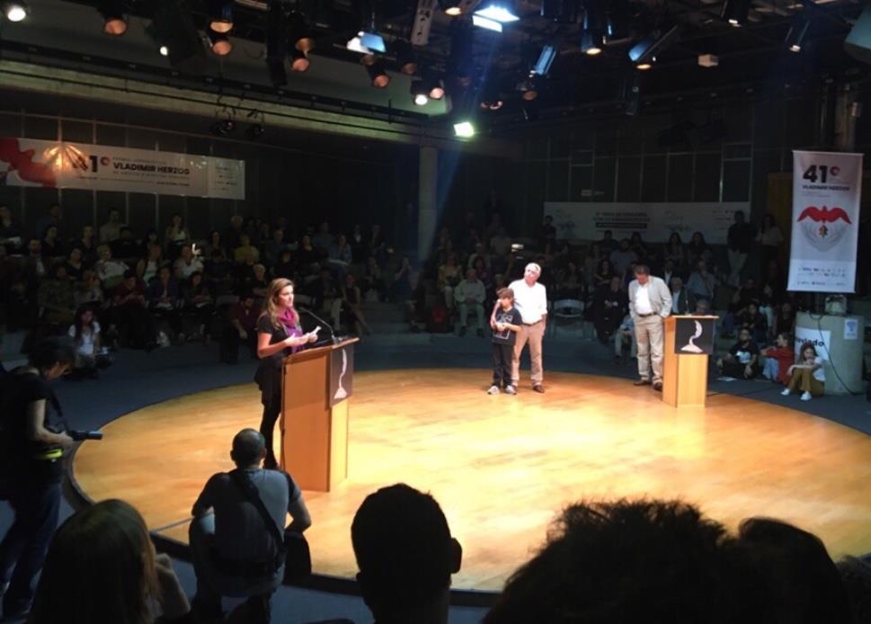 Patrícia Campos Mello em seu discurso acompanhada por seu filho, seu pai e o apresentador da premiação Juca Kfouri (esquerda à direita)