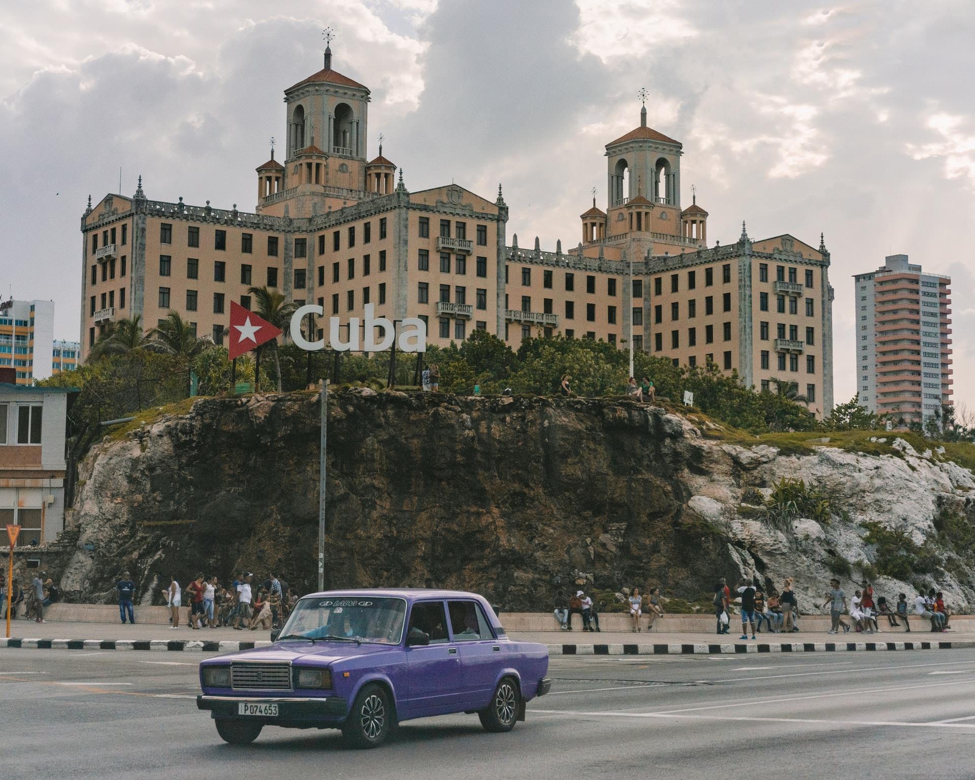 Fotografia de uma avenida da capital cubana, vê-se um carro antigo no centro da imagem.