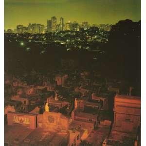 Cássio Vasconcelos -Cemitério do Araçá #3: Cemitério do Araçá à noite, com tons alaranjados à frente, mais escuros ao centro e com os prédio da cidade ao fundo. Assinada e datada 2001 e 2002. Tiragem 1/3, dimensões 30 x 29 cm.