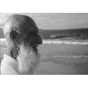 Observação: Homem velho, de longas barbas brancas, observando o horizonte na praia. Foto preto e branco. Dimensões 39 x 59 cm.