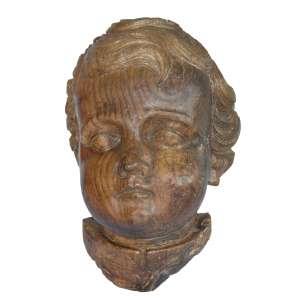 Cabeça De Anjo Barroco: Cabeça de anjo barroco em madeira, olhos amendoados, feição séria, cabelos lisos recolhidos sobre a testa e. Brasil ou Portugal, Século XVIII. Dimensões 48 x 24 cm.