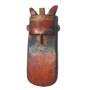 Máscara Africana Vermelha: Máscara em madeira policromada em tom vermelho escuro, orelhas pequenas em destaque e chifres sobre a cabeça. Olhos e boca são pequenos orifícios na madeira, dimensões 55 x 20 x 9 cm.