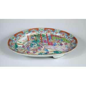 Grande travessa oval em porcelana Cia. das Índias ricamente decorada em esmaltes policromados no padrão conhecido como mandarim, com cena palaciana emolduradapor larga borda com reservas florais e estilizações geométricas. Período Jiaqing (1796-1820) – 49 x 37 x 8cm