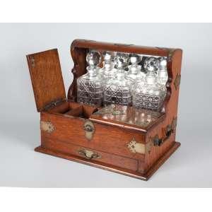 Licoreira de madeira e metal com 3 garrafas de cristal com tampas. Parte aberta com espelho e escaninhos. Alças laterais e gavetinha - 38 x 33 x 26cm - Inglaterra